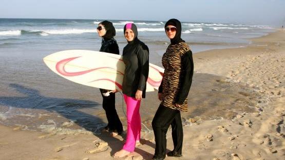 Islamic swimwear worn by three women holding a surfboard