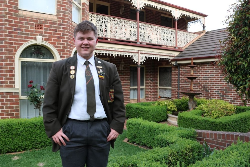 A young man in a school uniform stands in front of a house