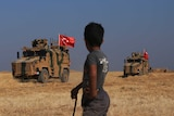 A boy holding a stick watches as a convoy of Turkish-flagged armoured vehicles drives past.