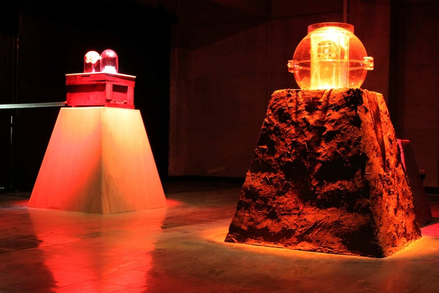 Two plinths, one made of wood with a red box and bulbs on top and one of compost with an orange bowl on top, in a dark room.