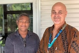 Two Aboriginal men stand smiling outside a building