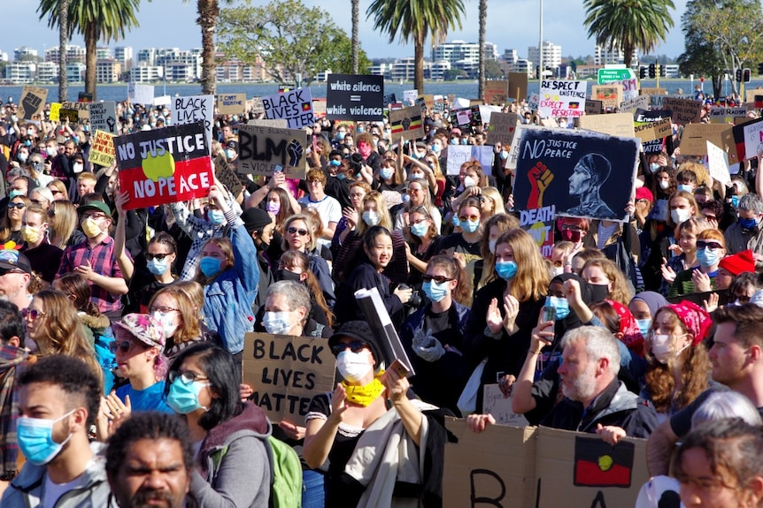 People stand in a crowd wearing masks and holding Black Lives Matter signs.