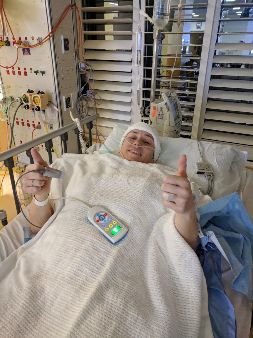 Cass Bennett is lying in a hospital bed with bandage around her head, smiling and giving two thumbs up.