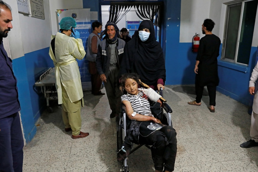 A woman pushes an injured girl in a wheelchair