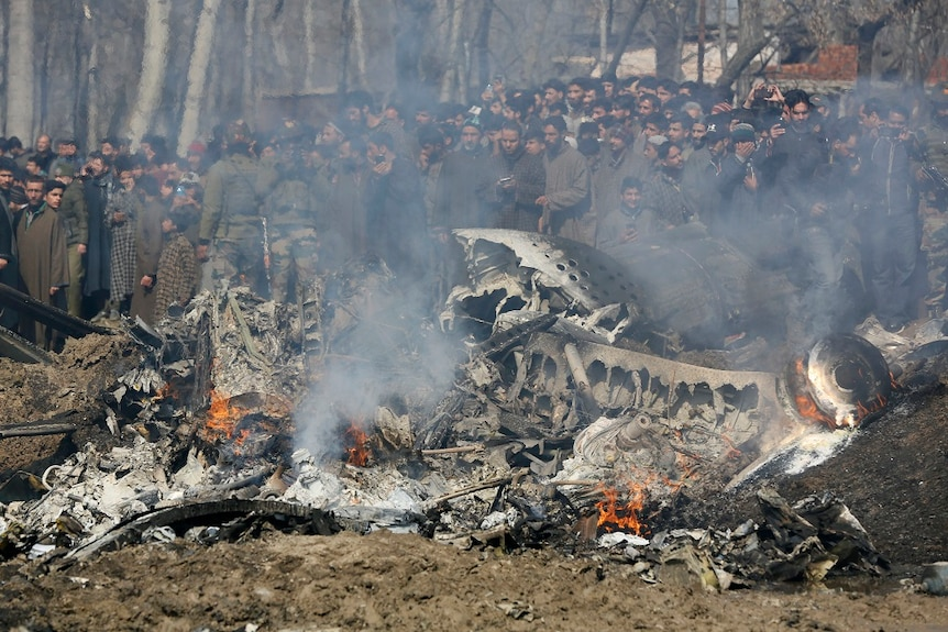 A large crowd gathers around the smoking wreckage of a downed aircraft