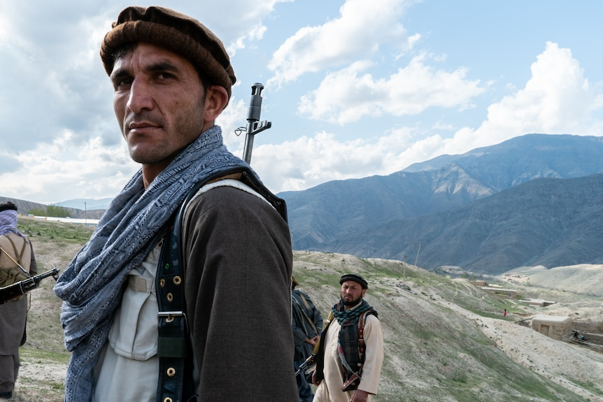 A man with a gun on his shoulder stands side-on to the camera with mountains and valleys behind him