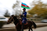 You view a man on a horse waving a Azerbaijani flag who is pictured mid-motion while riding down a main road.