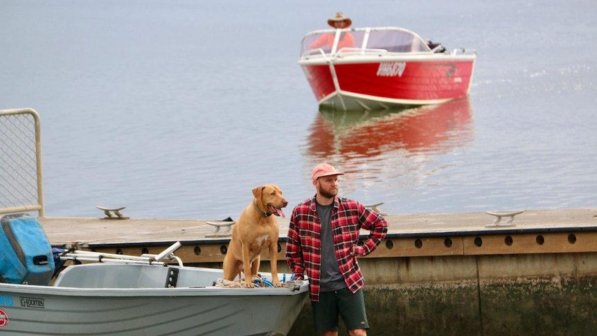 Man and dog stand beside tin boat