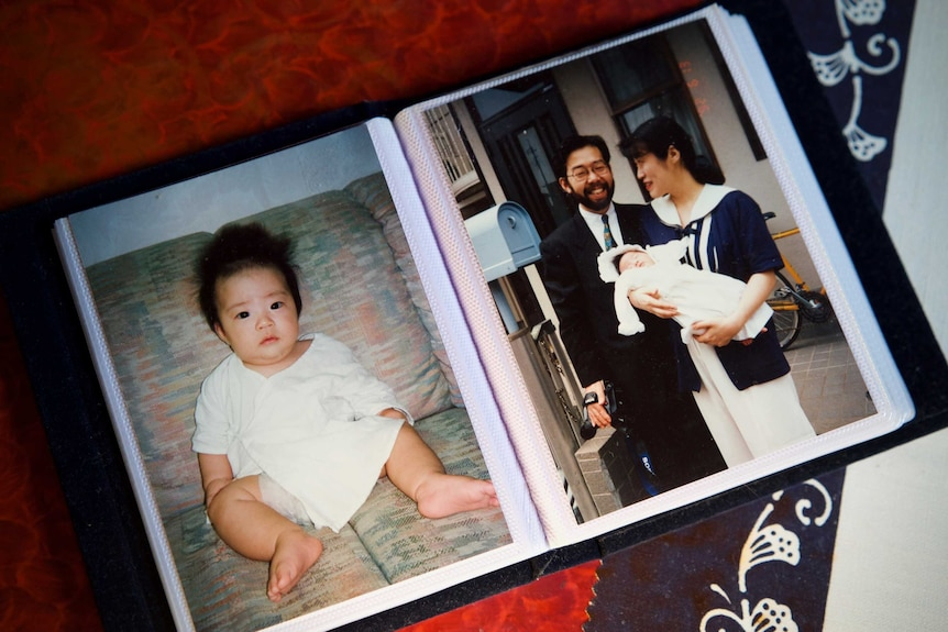 A photo album featuring a picture of a baby and a couple holding a baby together