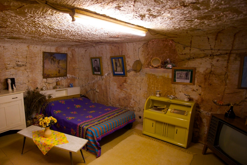 An underground bedroom in Coober Pedy with brown coloured walls made of rock and a bed.