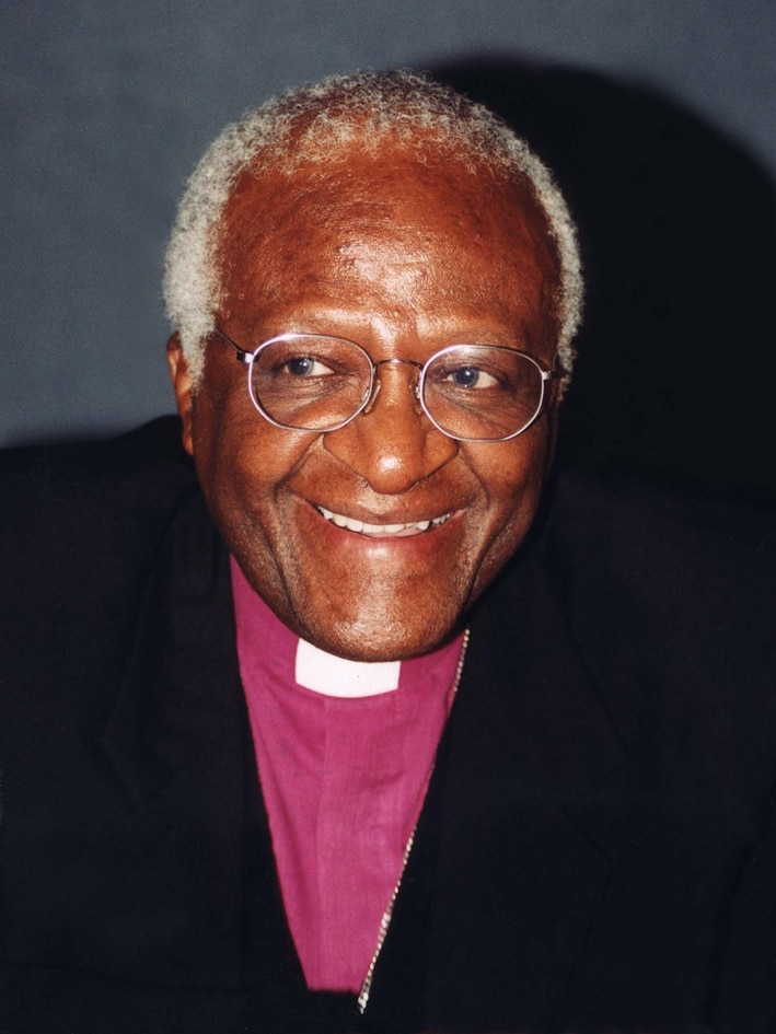 A close up photo of Desmond Tutu smiling in a clerical collar and black jacket
