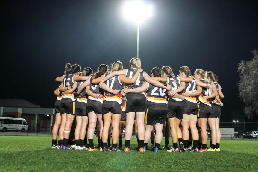 Bendigo Thunder women's AFL team in a team huddle under a floodlight