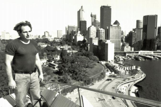 Black and white photo of Steve Tsoukalas standing on the Sydney Opera House sails