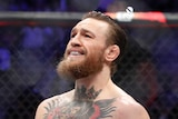 Conor McGregor smiles while kneeling on the octagon floor after defeating Cowboy Cerrone in UFC 246