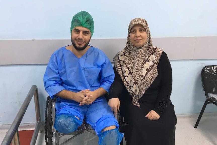 Ghadban sits next to his mother Amira.