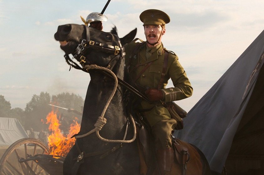 A moustached man in British allied colonel uniform sits atop a brown horse, pulling reins and with raised cavalry saber.