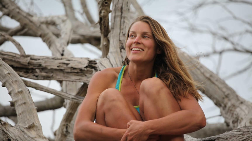 Woman smiling and sitting in tree.