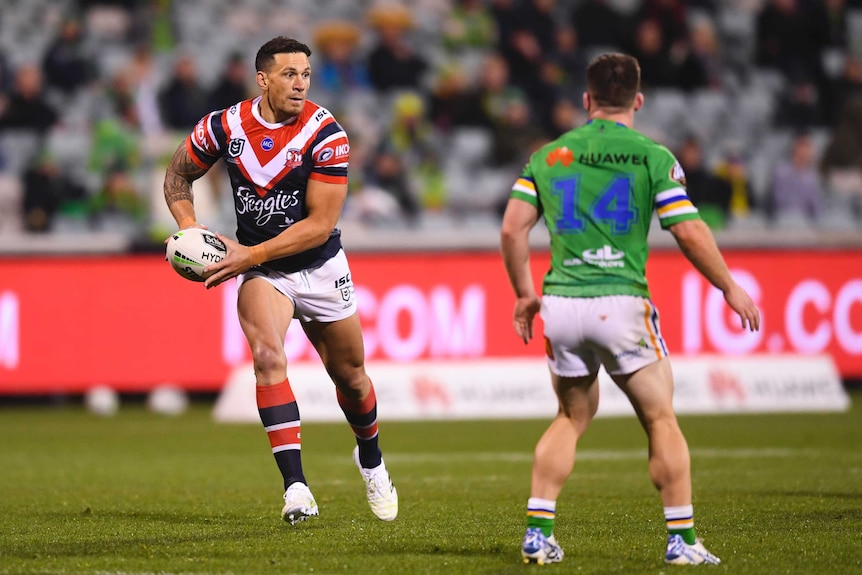 A Sydney Roosters NRL player holds the ball in two hands as he prepares to throw a pass against the Canberra Raiders.