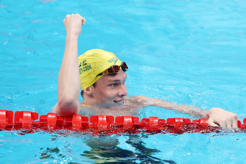 An Australian swimmer leans on the lane rope with a big smile on his face, punching the air with his fist after winning gold.