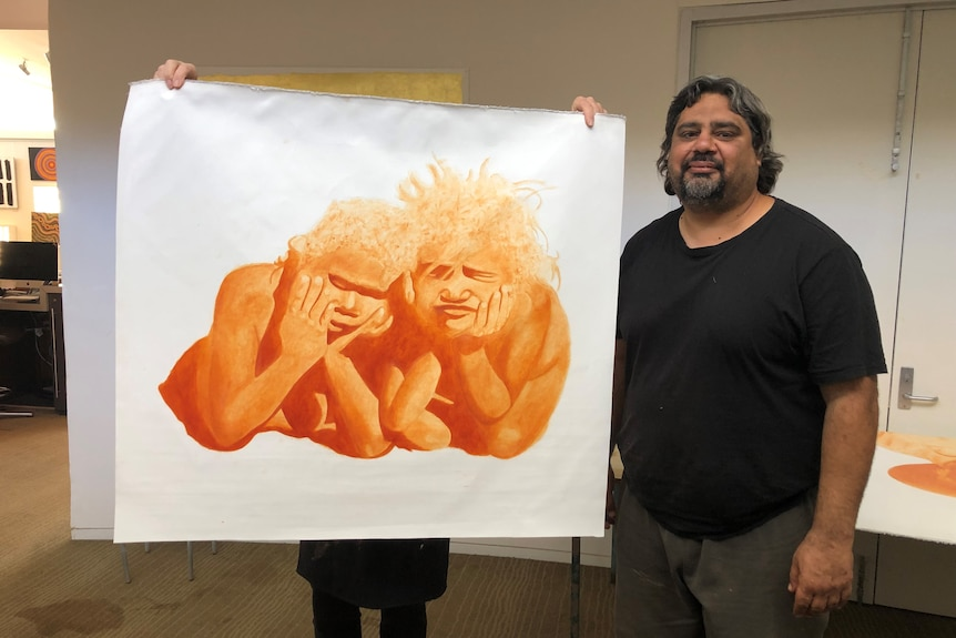 A man holds up a painting of two Indigenous people.