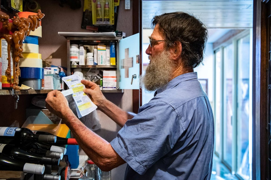 Don Firth compares a doctor's prescription with a box of medication in front of a packed medicine cabinet.