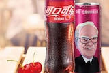 A cherry-flavoured bottle and can of Coca-Cola sold in China, with a cartoon of Warren Buffett's face on it.