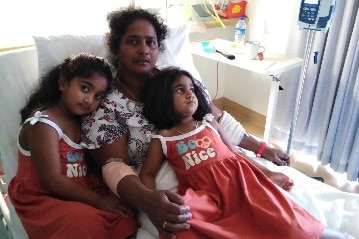 A woman lies in a hospital bed with two children lying on top of her. The girls are dressed in matching red dresses