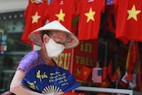 A woman walks past a row of T-shirts printed with Vietnamese flags in Hanoi.