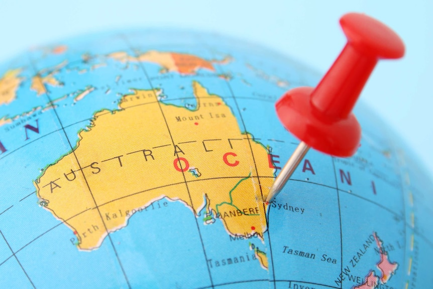 Pushpin points out Sydney in plastic globe.