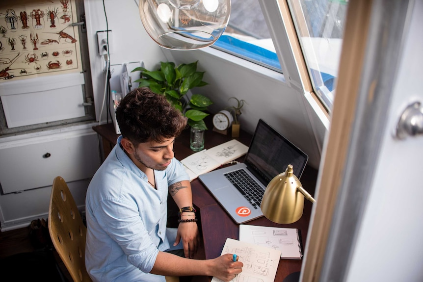 Man works on a computer in a home office space in a story about tax deductions you can claim if you work from home.