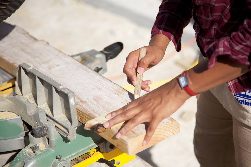 A close up of a female carpenter's hand marking up a piece of timber.