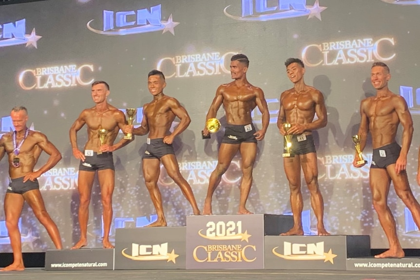 Noor on the podium with other body builders.