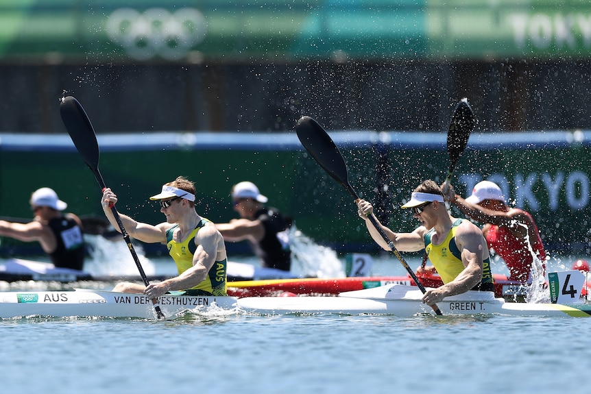 Two men in green and gold in a double kayak racing.