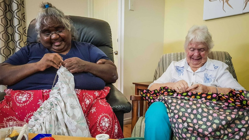 Two women sit in armchairs hand-sewing skirts.