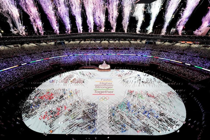 Fireworks explode of the Olympic stadium full of athletes.