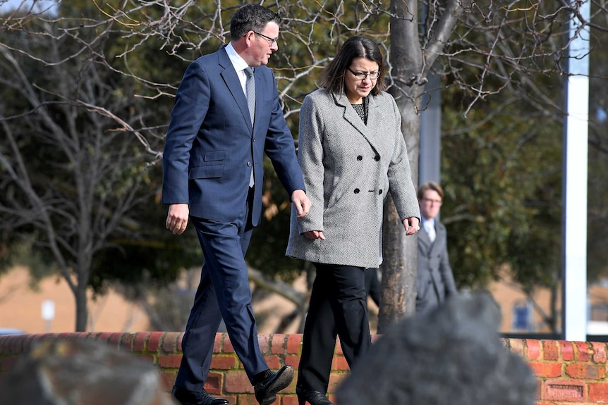 Jenny Mikakos walks alongside Dan Andrews on an outdoor path, surrounded by trees.