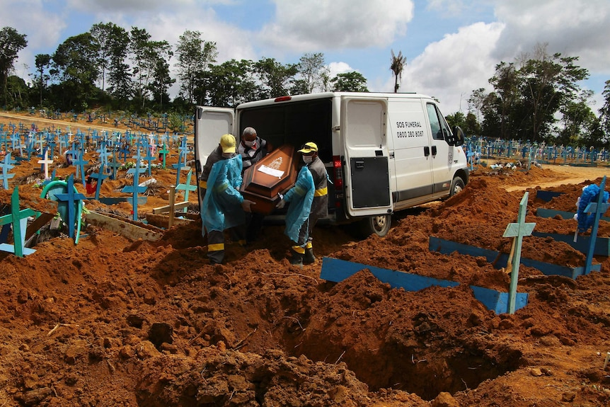 Funeral workers unload the coffin from the back of a van amid a cemetery riddled with crosses in Brazil.