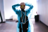 A woman in scrubs walking down a hallway with her hands on her head