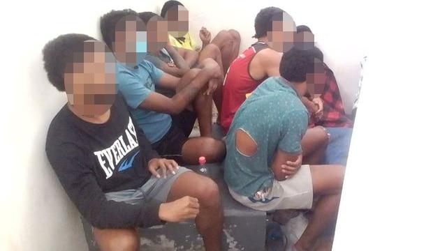 Men with faces blurred squat on concrete floor.