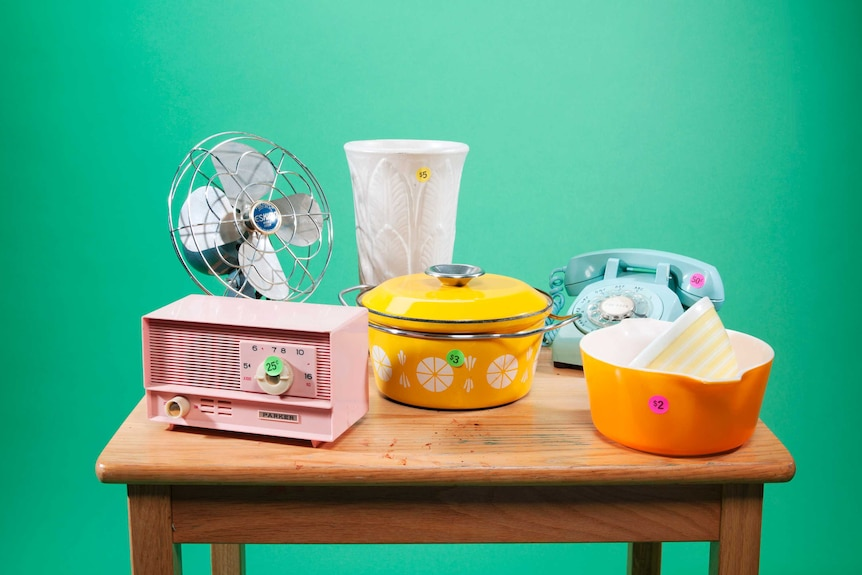 A fan, vase, radio, rotary phone and tableware are displayed on a wooden table with low-price stickers.