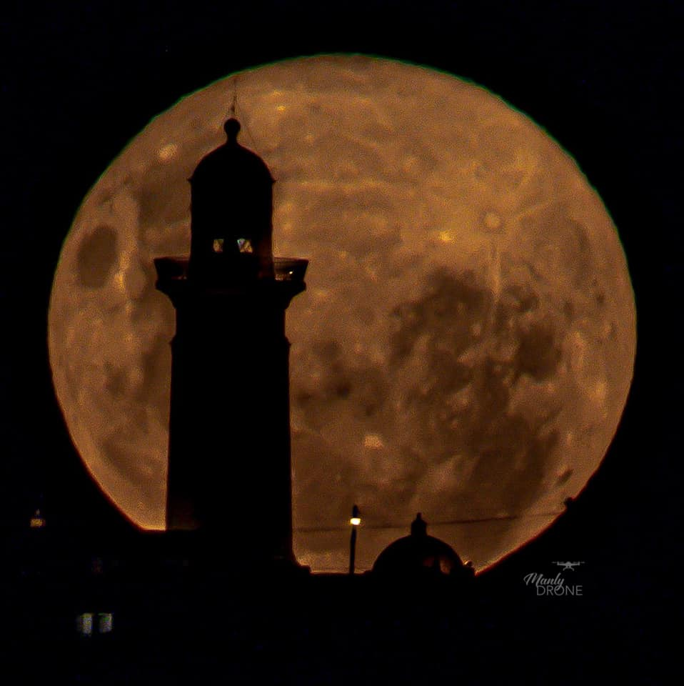 The moon behind the black silhouette of a lighthouse.