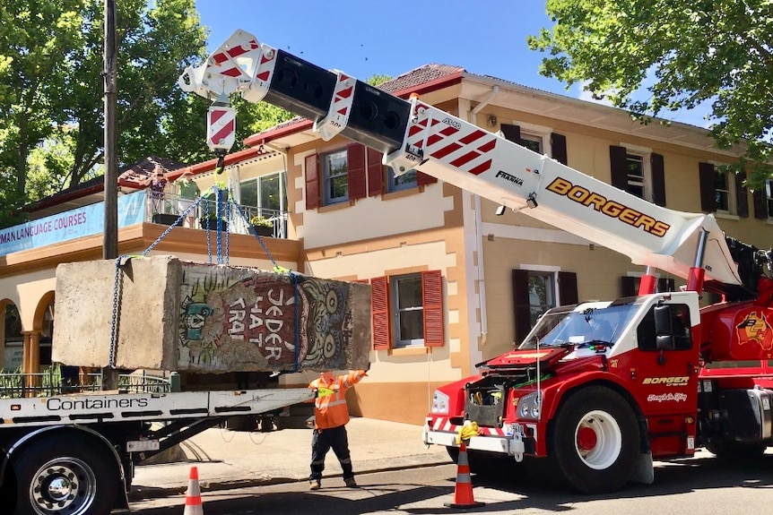 A graffiti slab of wall is being moved by a crane