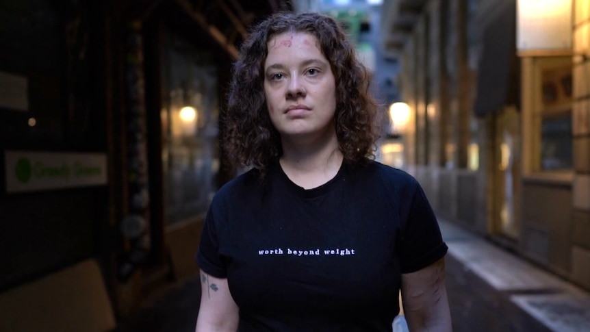 Person standing in a Melbourne laneway, wearing a black shirt that says 'worth beyond weight'.