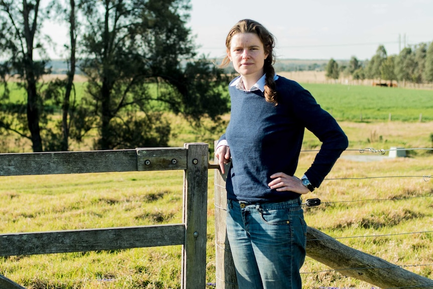 Georgina Woods leans against a fence in the countryside