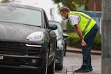 An official in a high-vis vest leans down to talk to a driver through the passenger-side car window.