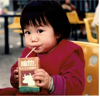 A young girl drinks milk out of a box that has Chinese writing and packaging.