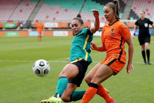 Female soccer players chasing down a ball with the opposition player behind her as they race for the ball during a match