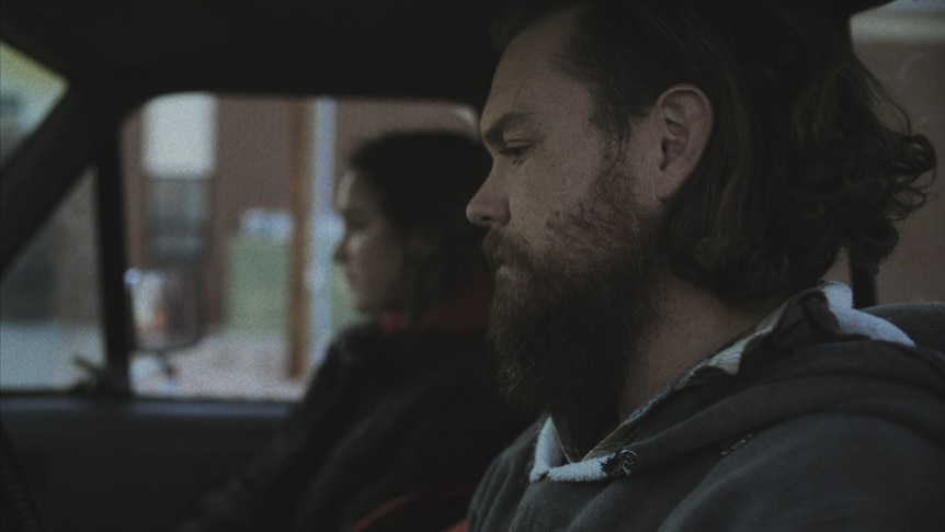 A man with beard and unruly hair sits in the front of a pick up truck, a woman sits next to him