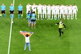 A person holding a rainbow flag faces the players during the playing of the Hungarian national anthem at Euro 2020.