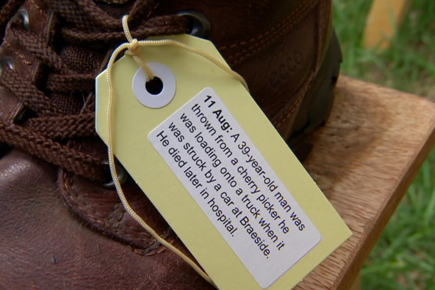 A shoe with a tag on it describing the circumstances of a worker's death.
